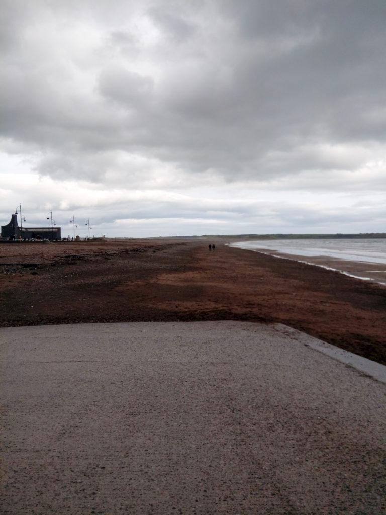 Dunkler Strand, dunkle Wolken.