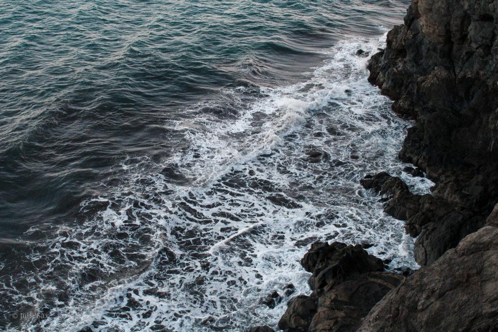 Die Wellen brechen sich an den Klippen.